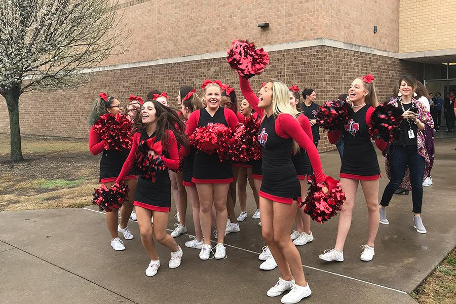 Waiting for team outside, the varsity cheerleaders celebrate the team's departure to state.
