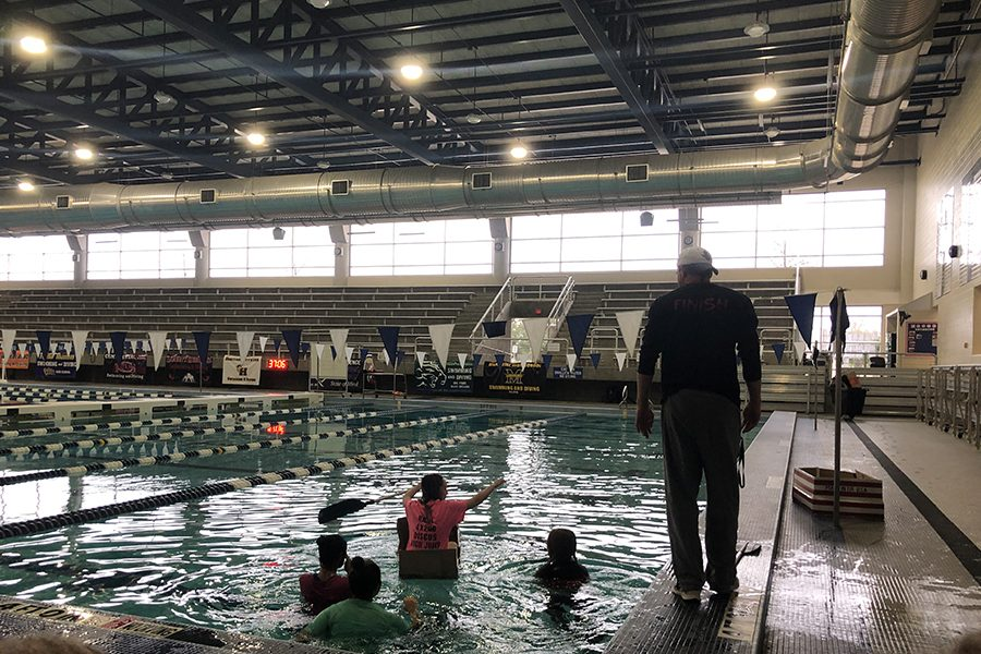 With+teacher+Justin+Koons+looking+on%2C+outdoor+education+students+try+to+row+their+cardboard+boat+from+one+side+of+the+pool+to+the+other+at+Bruce+Eubanks+Natatorium+on+Thursday%2C+Feb.+7%2C+2019.+