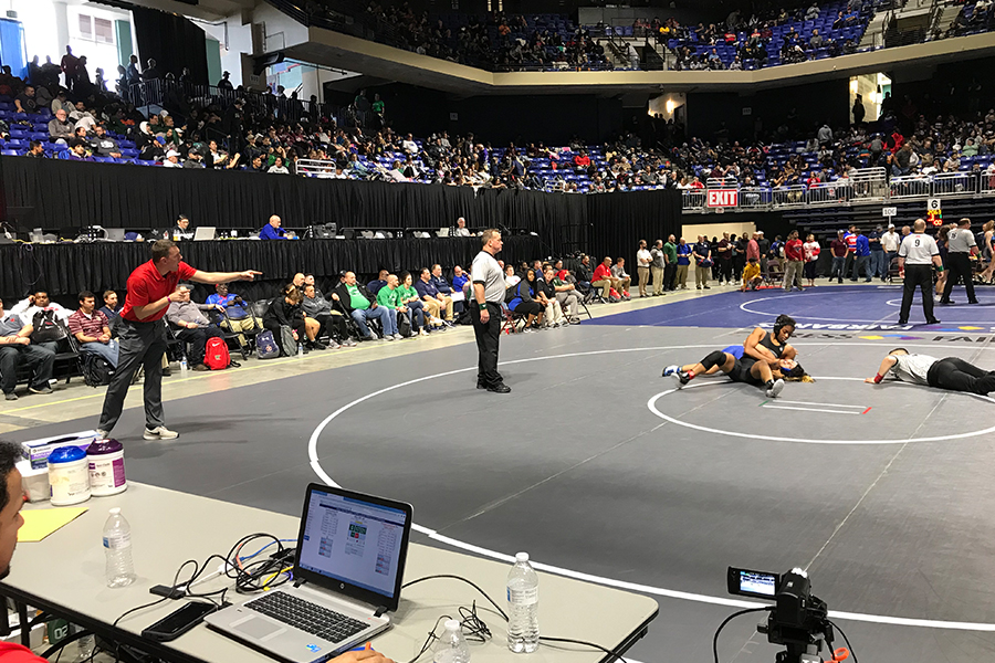 With+the+Redhawks+on+the+verge+of+getting+a+pin%2C+assistant+wrestling+coach+Justin+Koons+shouts+out+instructions+from+the+side+during+the+2019+UIL+State+Wrestling+Tournament+in+Cypress.+