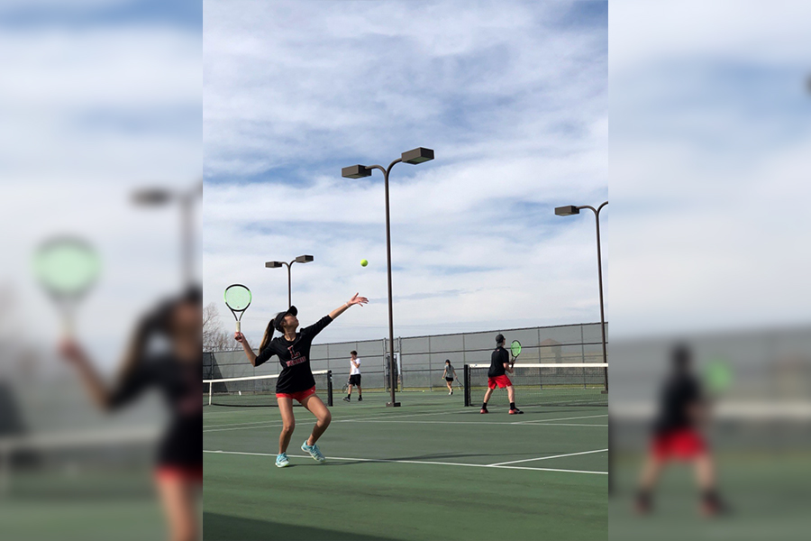 Freshman Tracy Ngyuen prepares to serve the ball over the net as senior Nick Heldman remains focused on the opponent. Tennis will compete in the District competition on Wednesday at Marcus High School.