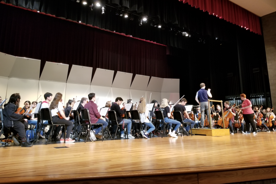 Redhawk+orchestra+students+sit+on+stage+in+the+auditorium+along+with+orchestra+students+from+Conway+High+School+in+Conway%2C+AR.+Conway+director+prepares+to+conduct+the+combined+orchestra+as+campus+orchestra+director+Julie+Blackstock+looks+on.