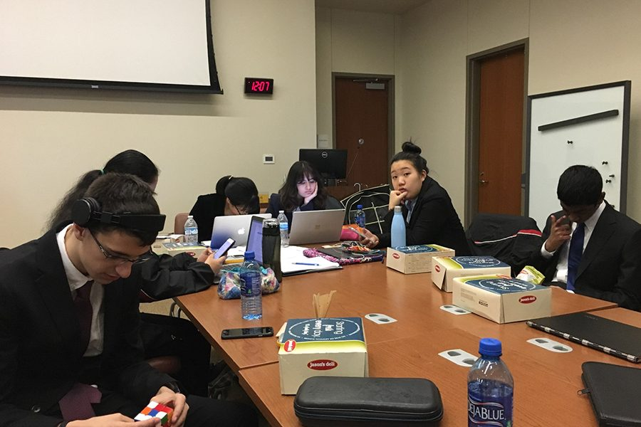 Academic Decathlon students gather around a table at a past competition in 2019. As per COVID-19 restrictions, AcDec competitions went online for this school year, including the Irving ISD Invitational Competition, where the team took home eighth place out of competitors from across the country.