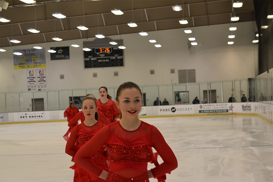 After finishing their routine to their program Fire, Molly Stephenson (9) stands second in line as they skate off the ice. They placed second on this routine. Stephenson started ice skating in third grade. Her interest in skating originated after seeing skaters at ice rinks.