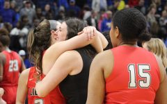 As senior Brittany O'Reilly-Ward (#15) looks on, assistant coach Kristin Lynch hugs senior Kelsey Kurak after the Redhawks secured a place in Saturday's 5A state championship game against Amarillo. The Redhawks got there after beating Kerrville Tivy 34-28 on Thursday, Feb. 28, 2019.