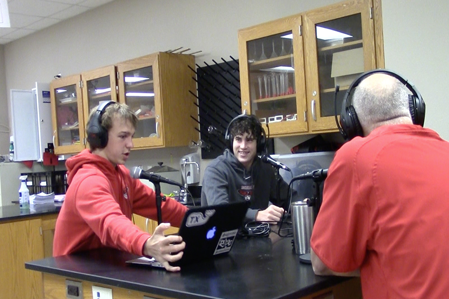 Recording their podcast, freshman Owen Wise, Joseph Hancock, and Ford Shippy interview assistant football coach Larry Swinnea in biology teacher Chris Ham's room.