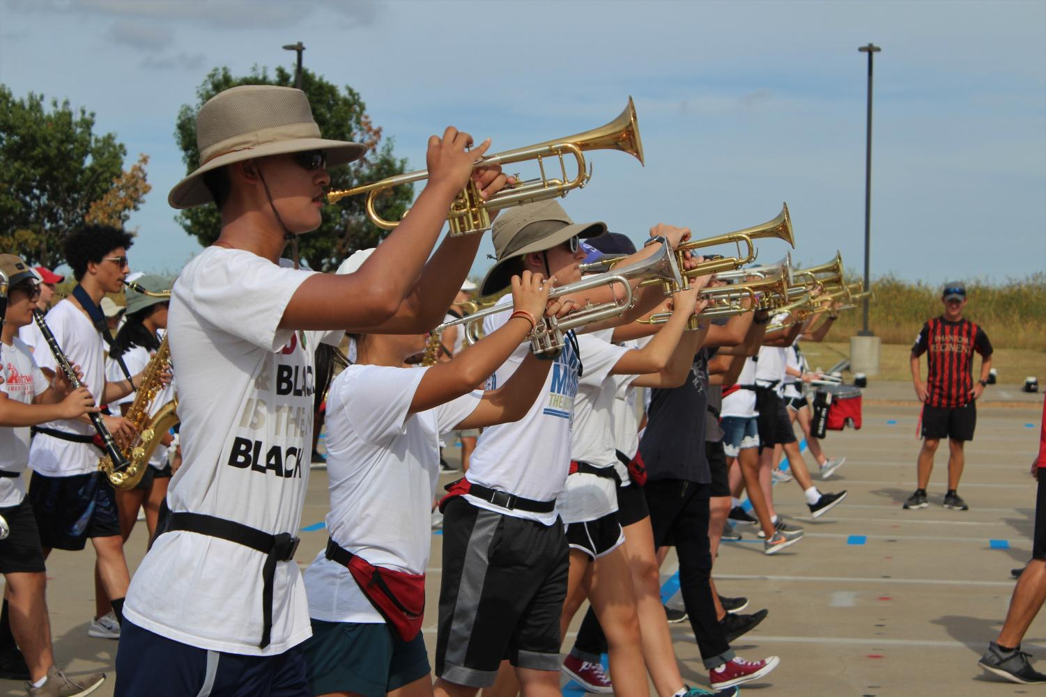 Band students practice their marching routine in the parking lot at a rehearsal after school. Marching band isn't the only program underway: students looking to try out for jazz band have the chance to audition this week.