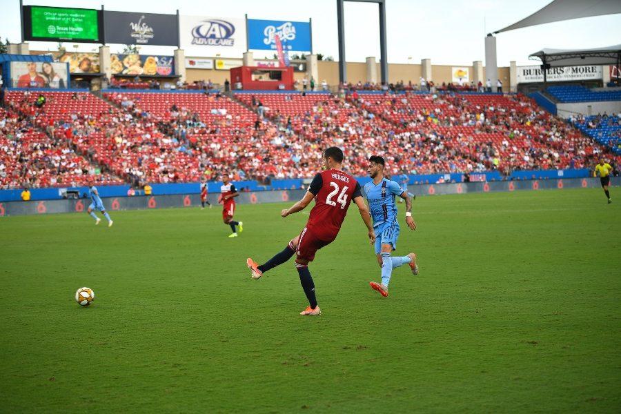 FC Dallas defender Matt Hedges (#24) kicks the ball with NYC FC's Valentín Castellanos following behind at Toyota Stadium on Sunday, Sept. 22, 2019.
