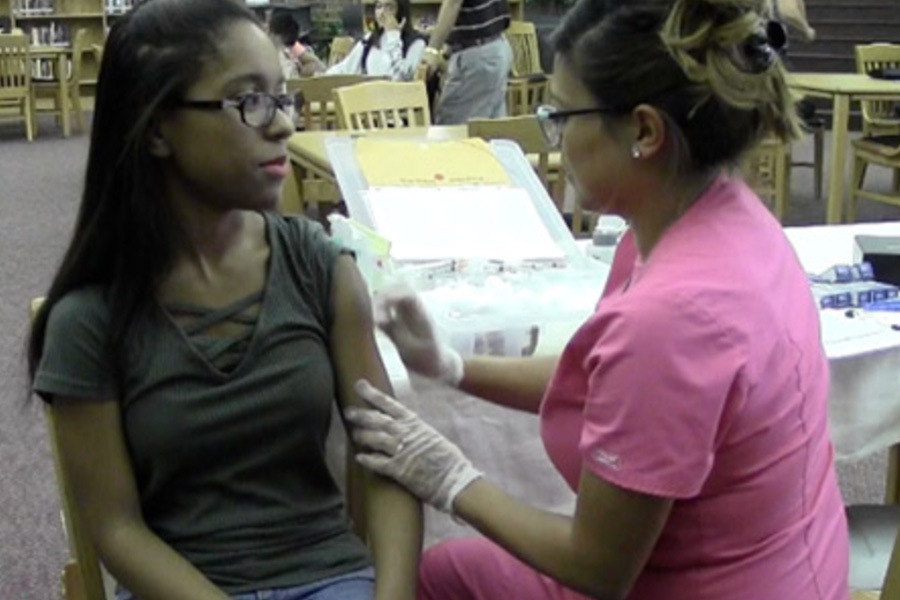 In a screenshot from a past WTV story, former Redhawk Aliza Porter receives a flu shot during Frisco ISD's flu clinic from a previous year. Frisco ISD is sponsoring its annual clinic on campus Tuesday from 3:30-6:00 p.m., delivering flu shots to all students and teachers, as long as minors are accompanied by a parent.