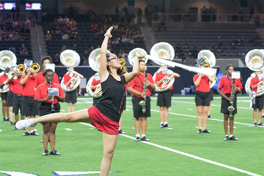 Junior Kimberly Nguyen waves her rifle prop around as a member of Color Guard during a football game at The Star. With marching band season coming to an end, color guard will compete int he UIL Area competition on Saturday in Little Elm.