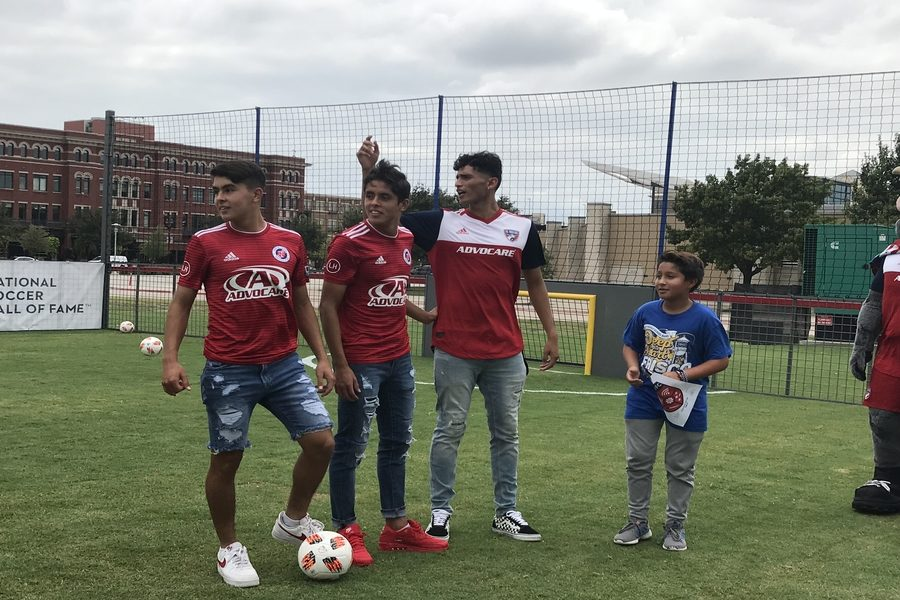 FC Dallas soccer players interact with FISD student on one of the complex
