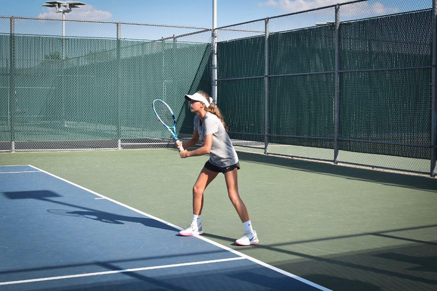 Freshman Milla Dopson prepares to retrieve the ball during a match. The tennis team takes on Reedy at 4:00 p.m. on Thursday at home.