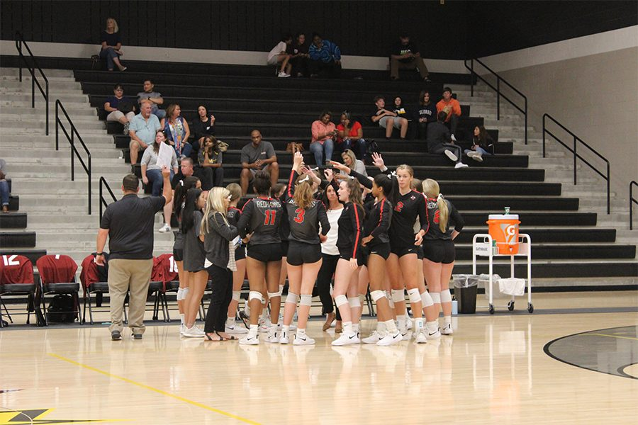 During a break in their district game, the varsity volleyball team meets with their coaches.