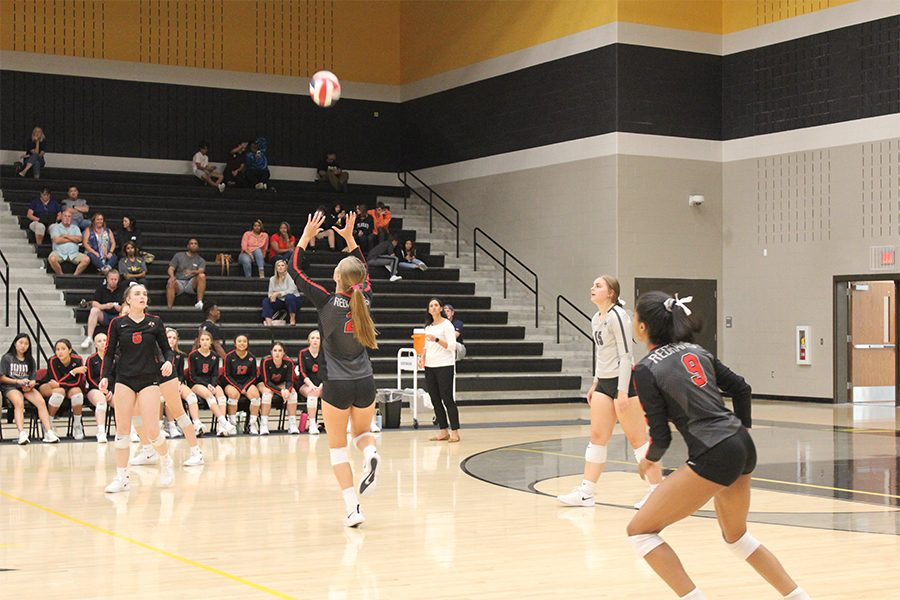 Senior Jenna Wenaas sets the volleyball during the varsity volleyball game on Tuesday September 10. The Redhawks defeated the Memorial Warriors 3-1, and look to continue their five game win streak on Friday against Lone Star at home.