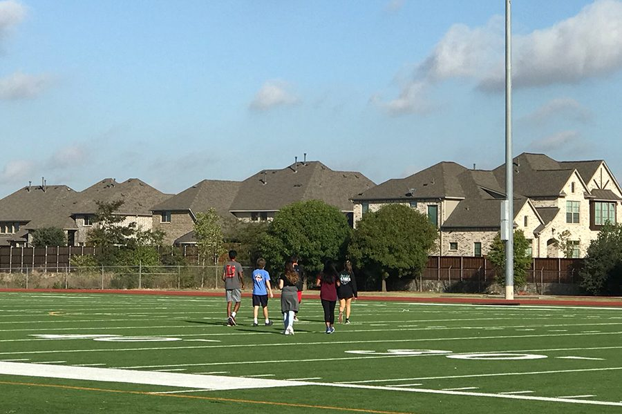 Freshmen Ashwin, Luke Martin, Mika Lal, Kyathi Uyyala, and Shannon Hogan walk across the football field, using their GPS to search for their checkpoints. Students taking AP Human Geography traveled to every corner of the campus, to participate in the class activity, geocaching.