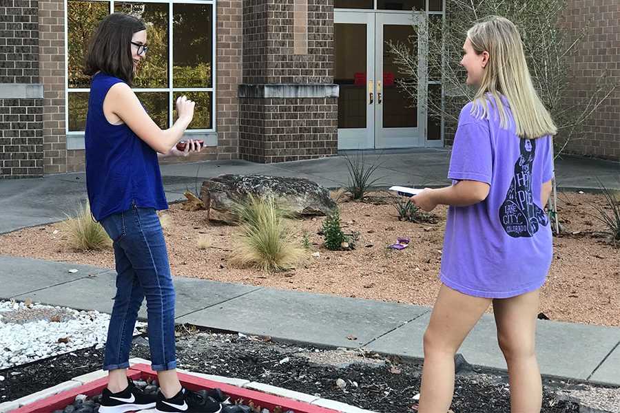 In an outside of the classroom learning experience, freshmen Olivia Paulk and Caroline Caruso collect locations and coordinates as part of the class' experience geocaching. AP Human geography has utilized the lesson for years, to teach students about GPS, and relate some of the class's terms to real life.