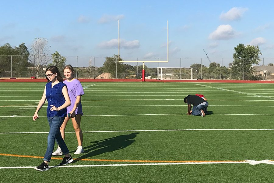 Freshman Olivia Paulk and Caroline Caruso walk across the football field hoping to find more of the desired coordinates , and possibly have the most in teh class. Students competed to find the most cashes located around campus using their GPS.