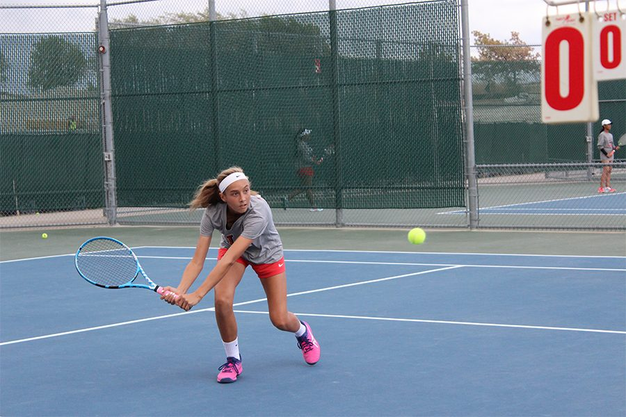 Freshman+Mila+Dopson+lunges+forward+to+hit+a+backhand+shot+at+a+match+against+the+Reedy+Lions.+Playoffs+for+team+tennis+start+Tuesday+for+Redhawks+against+Lovejoy+High+School.