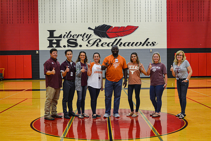 UT Austin and A&M alumni on the campus faculty pose in the gym. Redhawks have the chance to learn about both colleges tomorrow at the Texas Together Night.