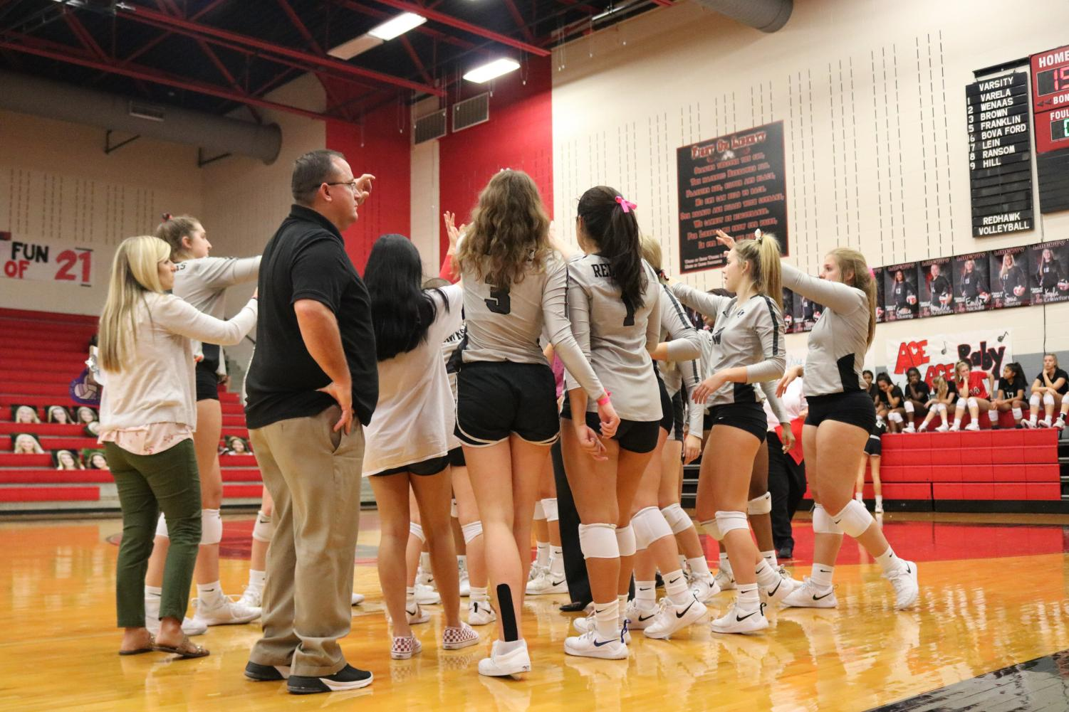 Redhawk volleyball players break out of a huddle at a home game. The team aims to keep their undefeated streak alive against the Titans at 6:30 p.m. at the Nest.