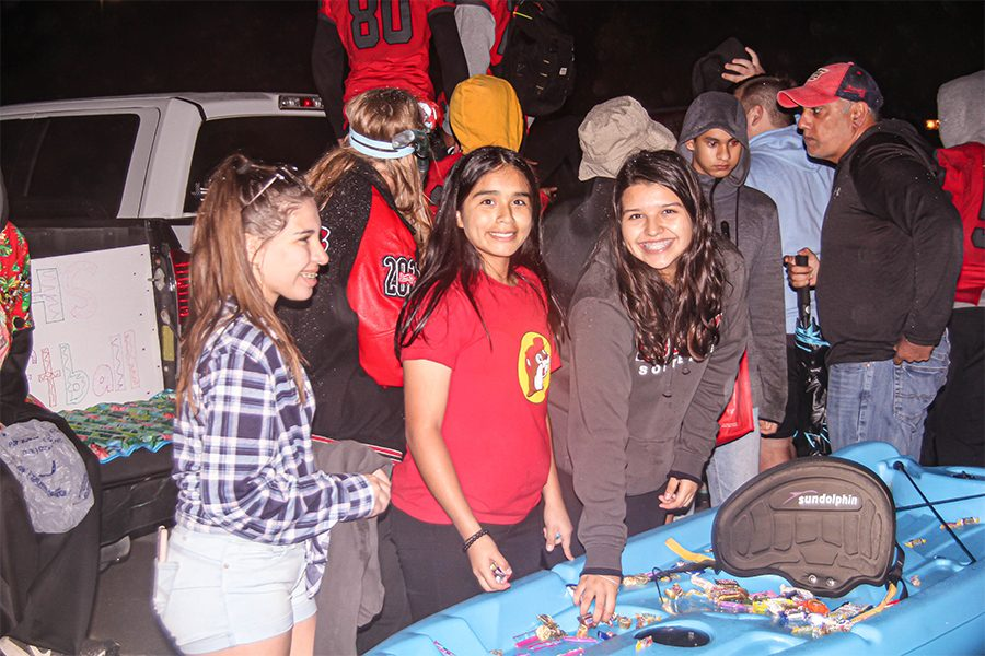 To get involved with the Halloween spirit, juniors Daniella Rodriguez and Kaylee Zuniga pass out candy at the annual Trunk 'r Treat event in the band parking lot. The event provides a safe way for kids to come get candy, along with promoting different clubs and organizations across campus.