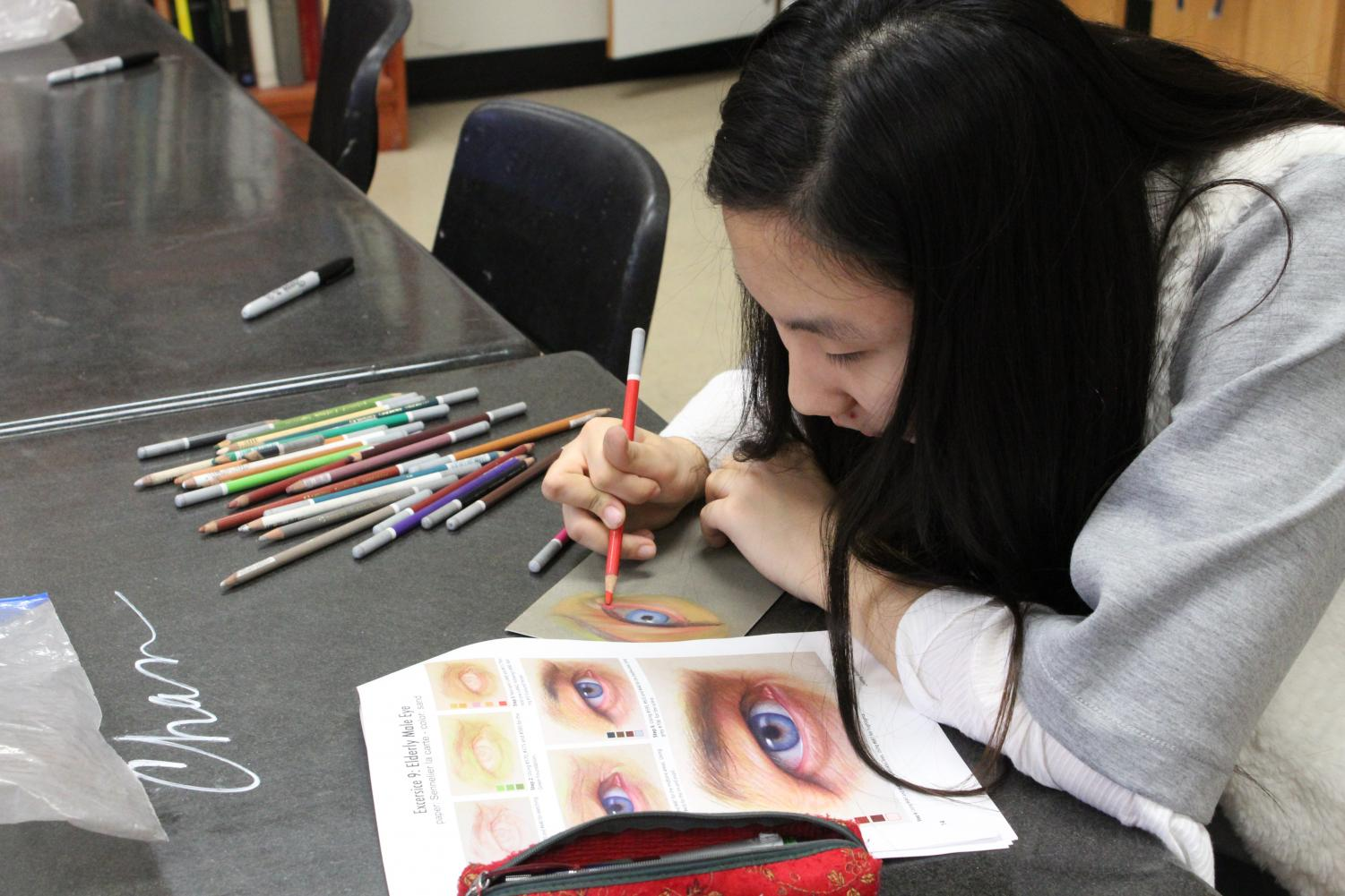 Elly Kong works on the technique of drawing a realistic eye with pastel pencils. AP Drawing students will use these techniques to draw realism portraits.
