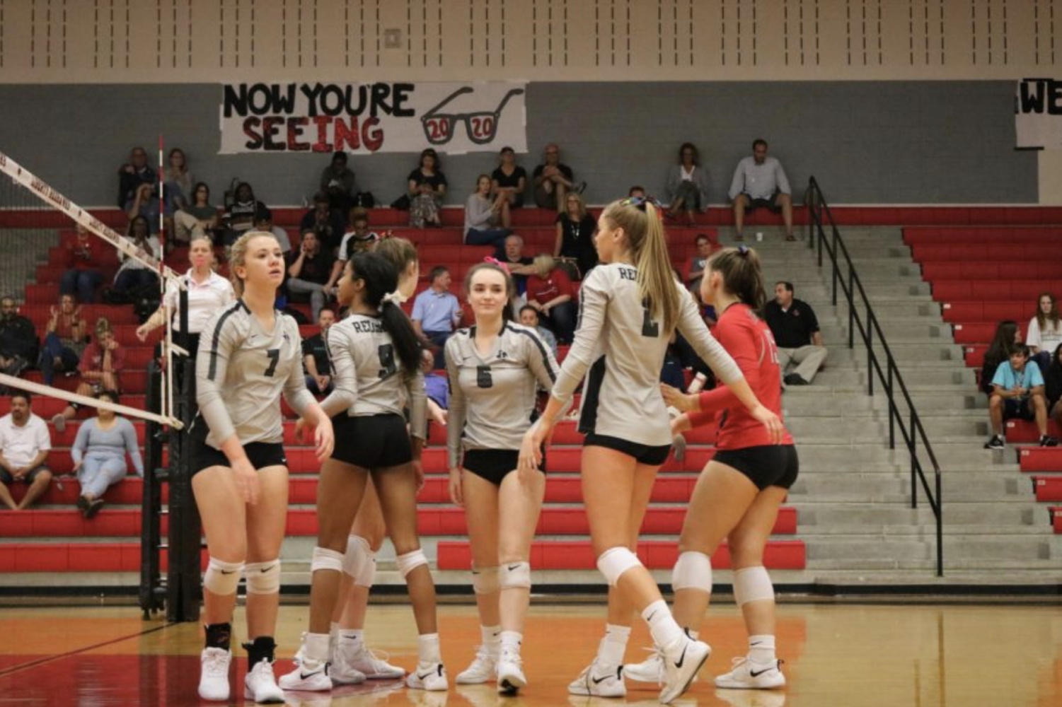 Cheering each other on, the Redhawks meet in the middle of the court after scoring a point. Volleyball will continue its playoff berth on Thursday against RL Turner High School.