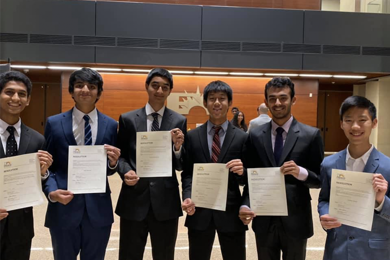 Students (from left to right) junior Tom Punnen and seniors Kapil Rampalli, Keshav Narasimhan, Johnathan Peng, Kunal Dhawan, and Zachary Suzuki hold up certificates. The six Redhawks were among other students honored at the school board meeting Monday night for receiving a perfect score on the SAT or ACT.