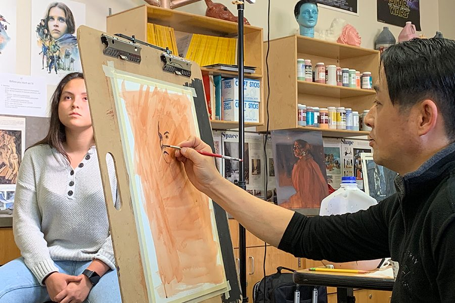 Steve Ko begin to outline junior Emma Varela in order to teach art students how to paint the human head through a live acrylic painting.