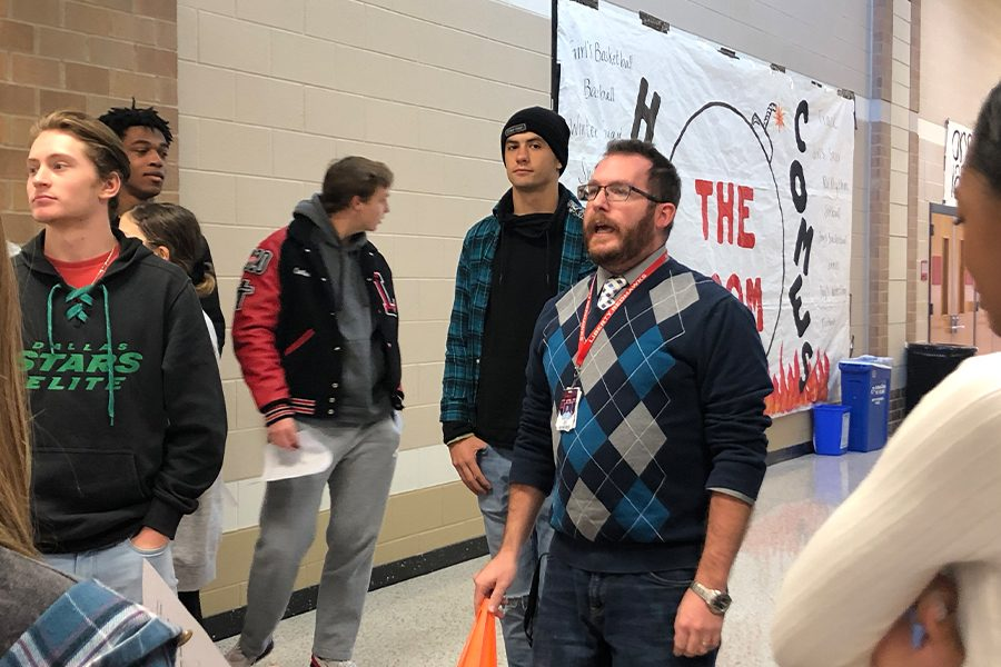 Astronomy teacher Kenric Davies directs students by the gym during an activity to represent a scale of the solar system. Davies hopes students gain a stronger understanding of distances between planets by modeling them outside of the classroom.