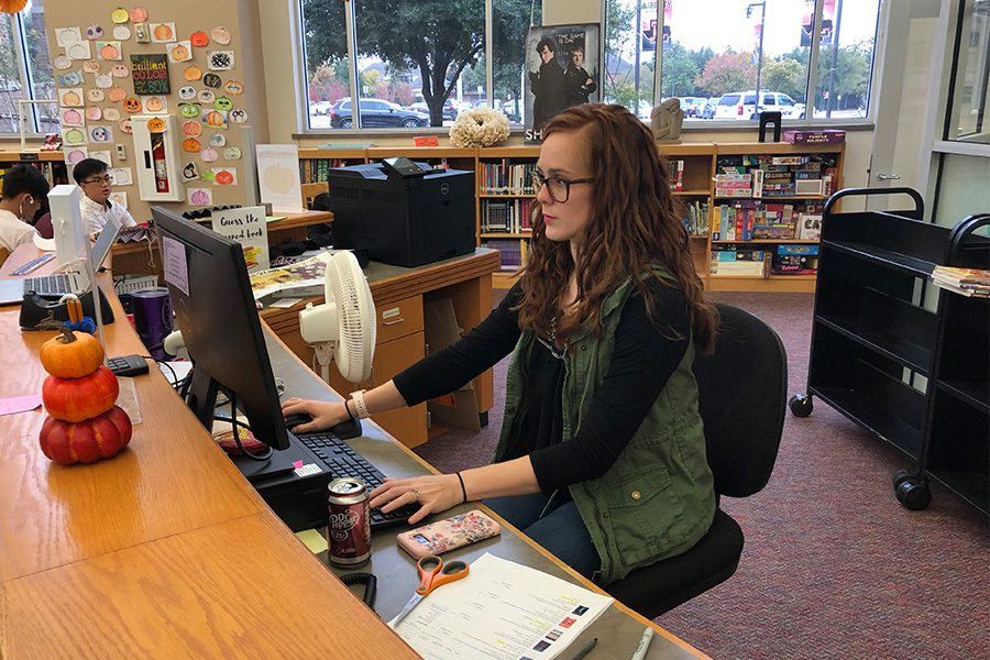 Librarian+Chelsea+Hamilton+reads+a+book+review+at+the+circulation+desk+in+the+library.+Students+who+write+a+book+review+can+earn+service+hours+if+submitted+through+the+library%27s+website+and+meets+a+500+word+minimum.+