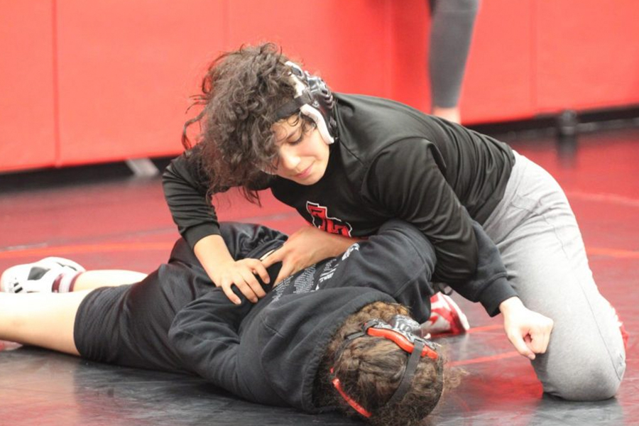 Senior Karina Quiros Zarate (top) takes down senior Emily Corona (bottom) during practice. With their season just kicking off, wrestling prepares for three consecutive days of dual starting Thursday, Nov. 21, 2019.