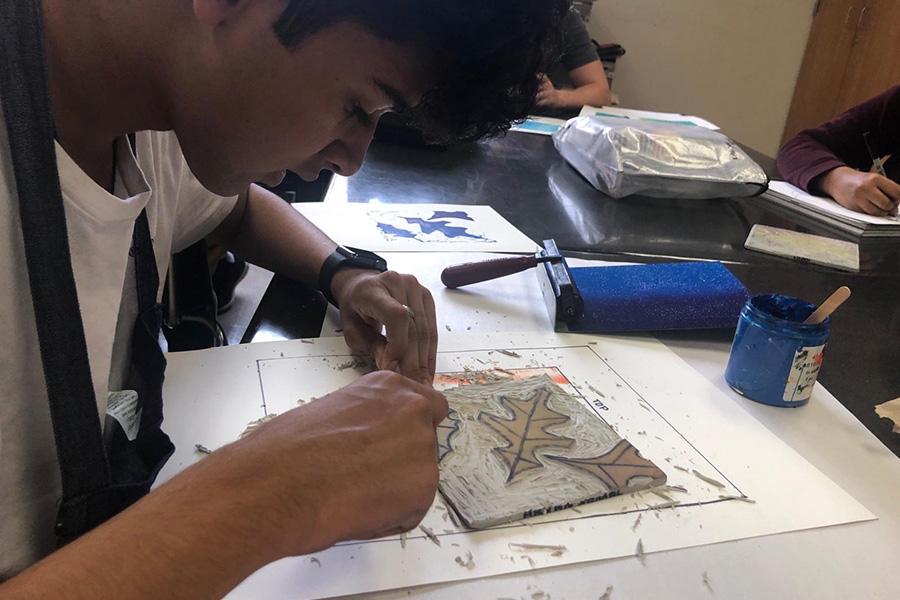 """Sophomore Aryan Samal works on his linoleum carving project. """"It'll probably take us more than two weeks to complete. There's a lot of thinking that goes on, mostly because you only have one chance to carve and any mistakes you make are final,"""" art teacher Pernie Fallon said."""
