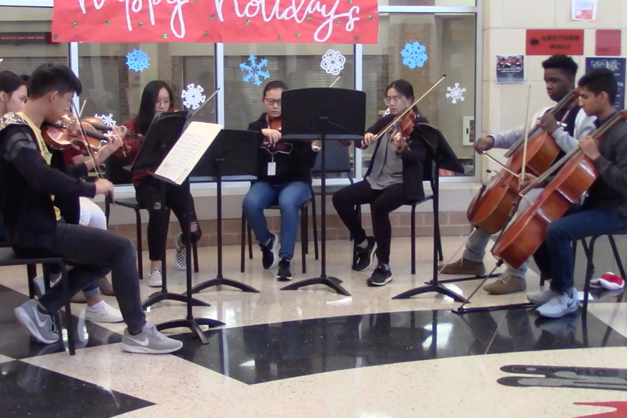 Spreading holiday cheer, the orchestra set up a small ensemble in the rotunda to play a few songs before school last Friday. They will return with more music on Friday 15 to continue the tunes of the season.
