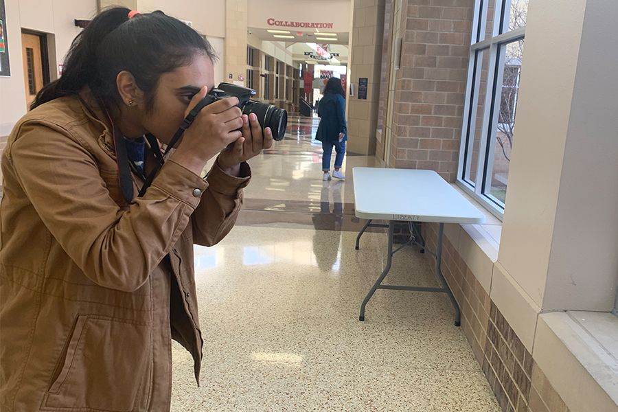 """Freshman Harshitha Suryadevara takes a picture for her 25 day project in photojournalism. """"Basically its giving a theme every day for 25 days that a student can interpret however they want to and take a photo of something related to that topic,"""" photojournalism teacher Kim Breen."""