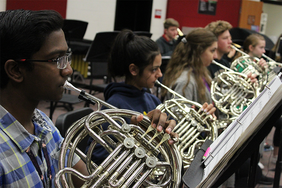 Sophomore Aravind Dharmalingam plays French horn alongside fellow band members during class. Band received their competition music in July with  area auditions held Coppell High School on Saturday.