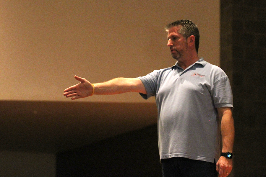Greg Chatmon, photographer for Southern Images, directs students into rows in the auditorium.