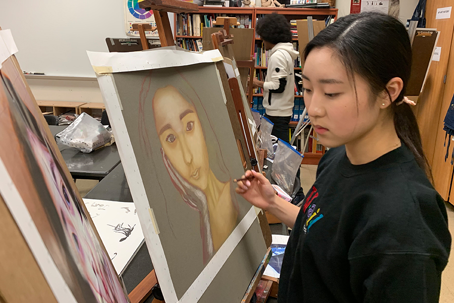 Senior Lauren Tanghongs paints herself for the pastel portraits project in AP Drawing. Other than using pastels for a change, students learned how to incorporate the skill of realism in their pieces.