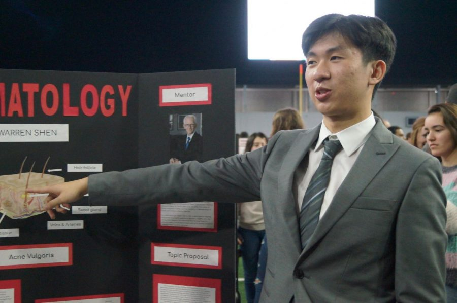 Junior Warren Shen points to a diagram of the skin as he presents his information. Shen is studying dermatology for ISM.