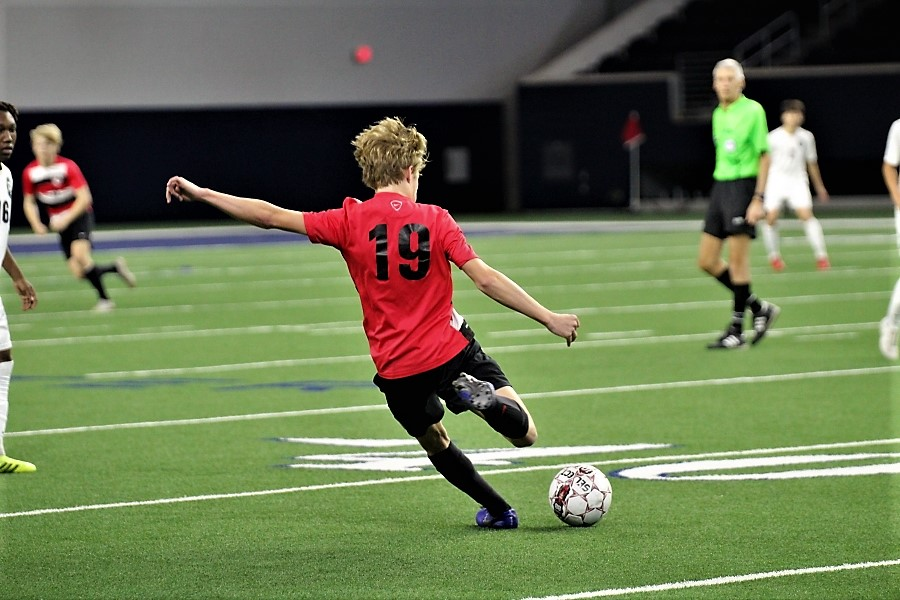 About to kick the ball down the field, junior Luke Enlow and the rest of the boys' soccer team scored their first win on Friday, Jan. 17, 2020 at the Ford Center as they beat the Reedy Lions 3-2.