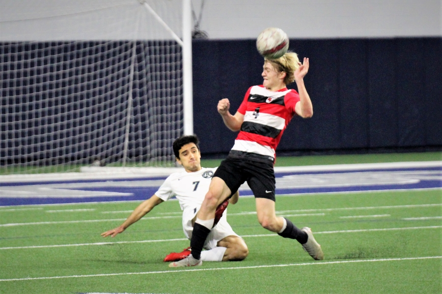 Heading the ball, sophomore Jack Bryan stands strong as a Reedy soccer player dives underneath him. The girls' side plays Heritage at home at 7 p.m. while the boys begin play at Heritage at 7:15 p.m.