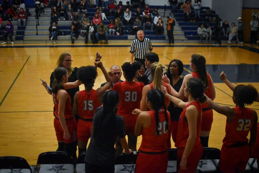 During a timeout, the girls' team reaches their fists into the huddle before breaking.