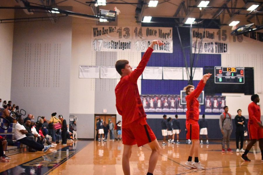 Warming up for the game, the boys' team practices their shooting form.