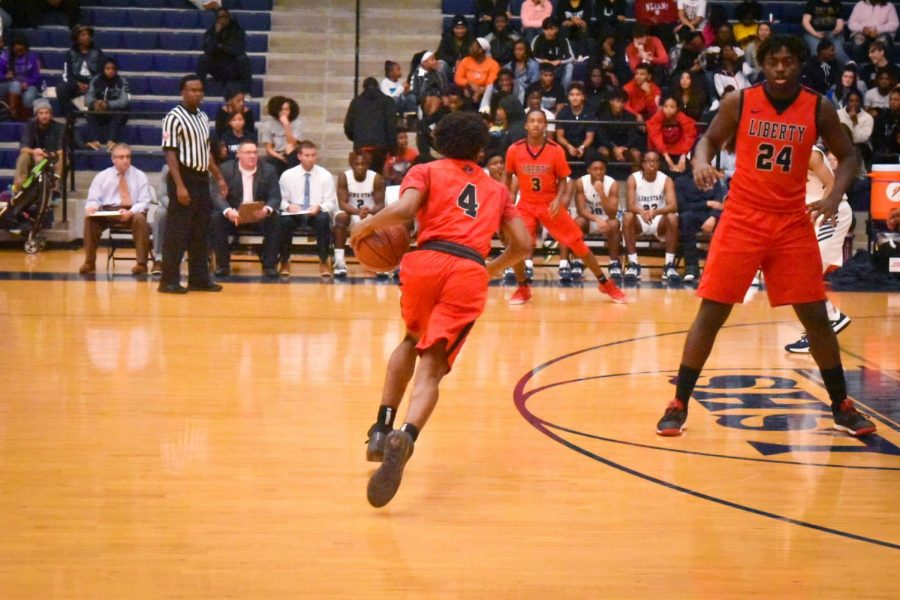 Dribbling the ball down the court, junior Trey Walter looks to make a pass. The boys' team kept their winning streak alive Tuesday night, while the girls had their first loss in district play.