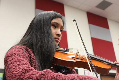 Practicing with the orchestra before social distancing orders, sophomore Christine Verzo follows the music. Students looking to join orchestra or participate in another year will still have the opportunity to audition online, instead of the traditional audition process in person.