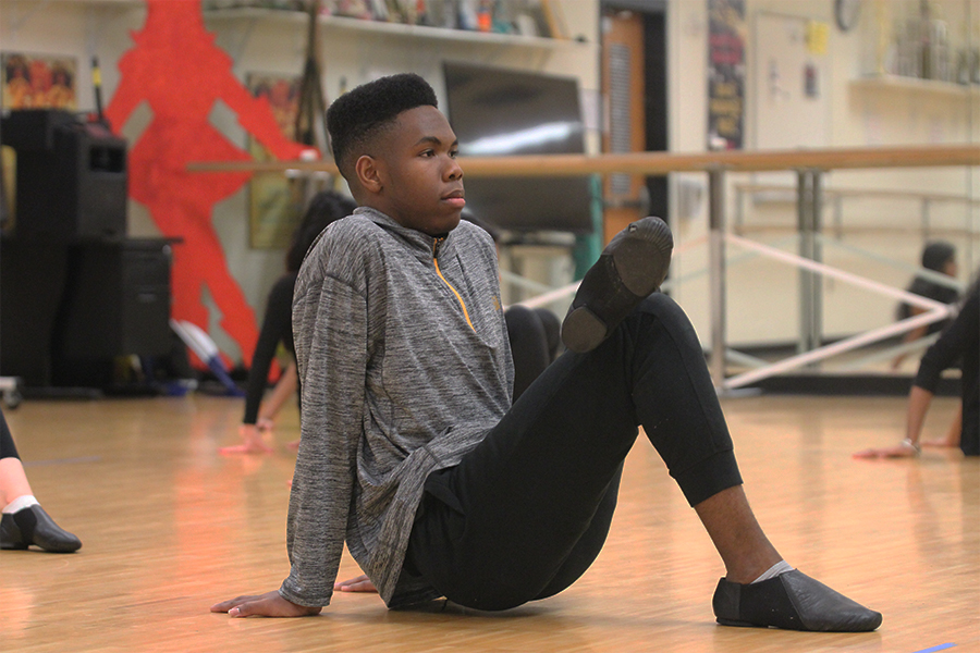 Kameron Askew, junior, leads his classmates in his Dance III class in stretches and warm up.