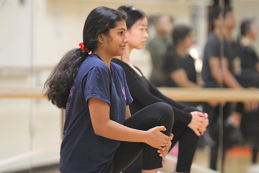 Being apart of Dance III, junior Ashika Deshpande and sophomore Michelle Jaeger stretch their left leg as a part of warmup.