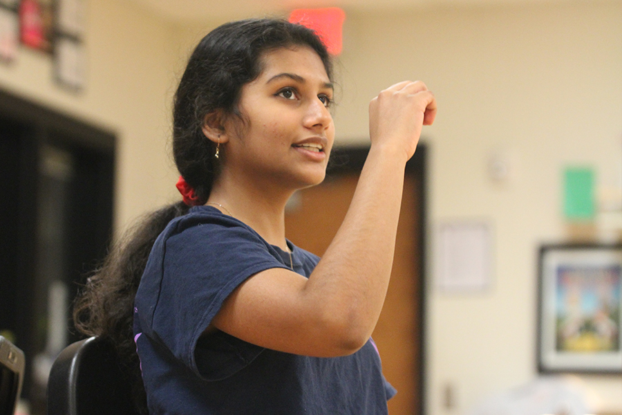 Sitting in a chair dancing, junior Ashika Deshpande is practicing her new Dance III choreography taught by Sarah Cadungug.
