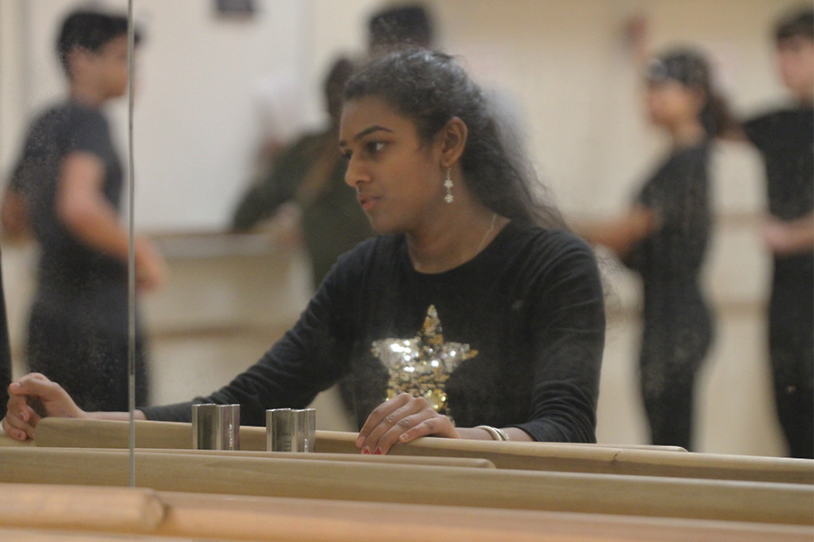 Holding the ballet bars, junior Sathyashri Muruganandam looks at herself in the mirror. She is warming up in her 4a Dance III class taught by Sarah Cadungug.