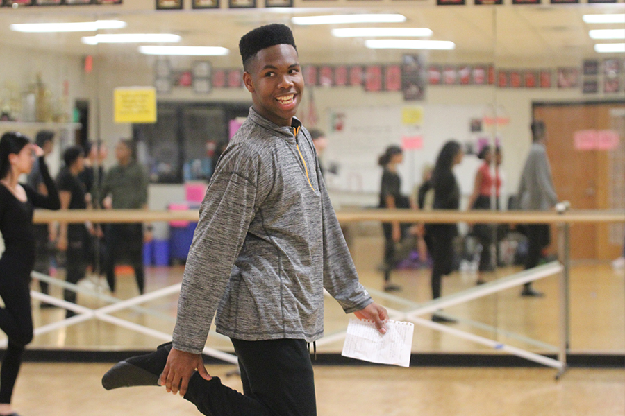 Junior Kameron Askew smiles back at his classmates in his Dance III class. Askew is leading warmup and gets to choose the stretches they do.