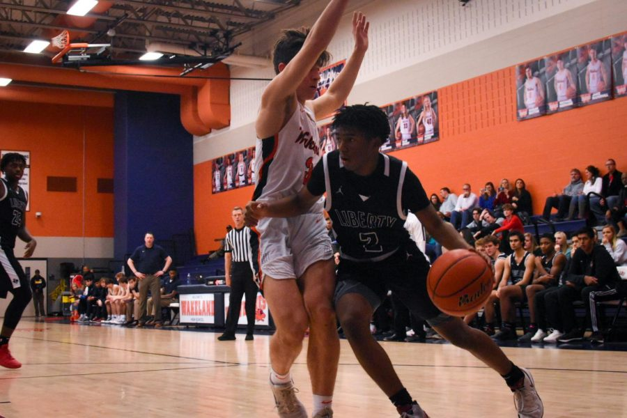 Trying to break through the Wolverine defense, junior Trey Walters dribbles the ball at Tuesday's game against Wakeland. The boys play their final home game at 7:15 p.m. at the Nest.